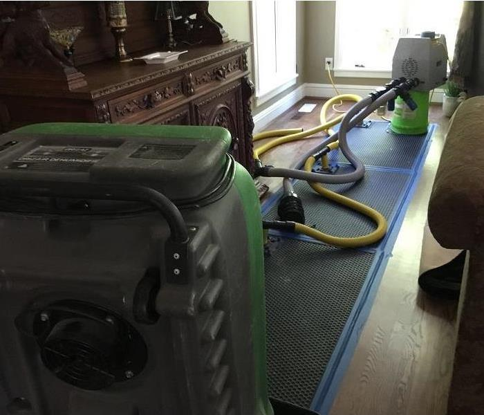 Room of a home with drying equipment set up on hardwood floors.