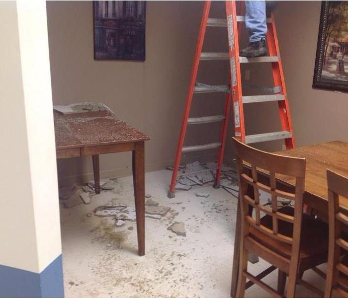 Room with tables, chairs, and man on ladder with dust and debris scattered on floor and table.