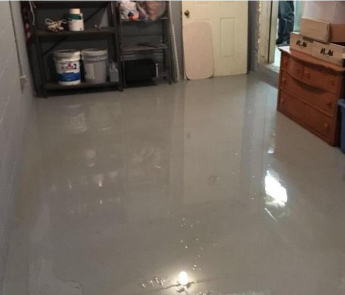 Room of home with gray hard-surfaced flooring showing standing water.