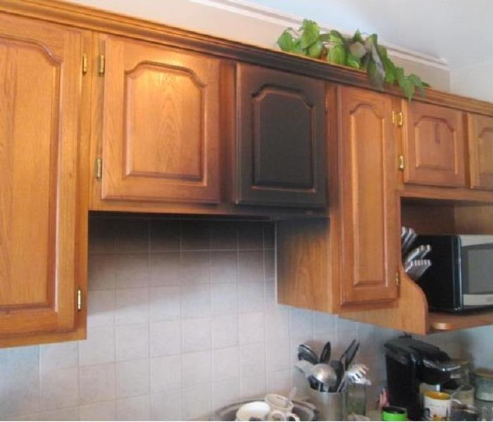 Wood cabinets in a kitchen covered with black soot.