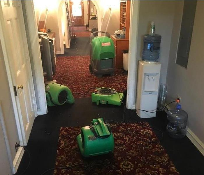 Carpeted hallway with water cooler in the corner and a dehumidifier and 3 air movers sitting on the floor.