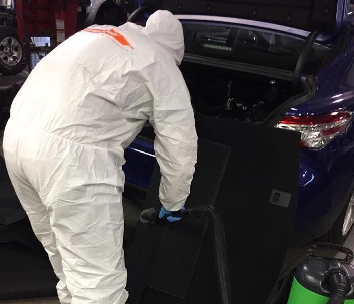 Man in white suit working in the trunk of a car.