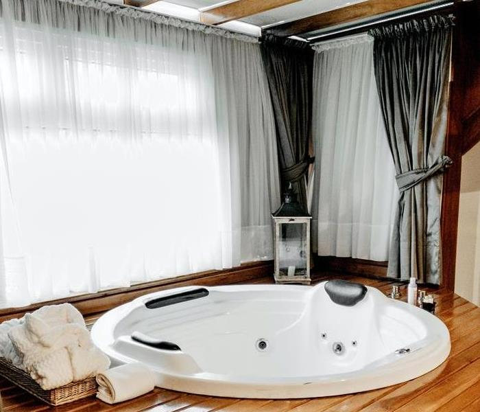 Jacuzzi tub surrounded by hardwood flooring